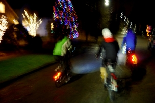 Tree Hauling on Bikes with blurry Christmas lights